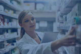 Female pharmacist is searching medicines on shelves with blue filter