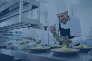 Smiling male chef working at kitchen with blue filter