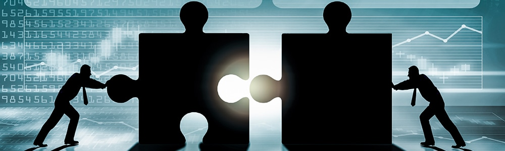 two people put two big puzzle pieces together and is symbolic for EDI mapping